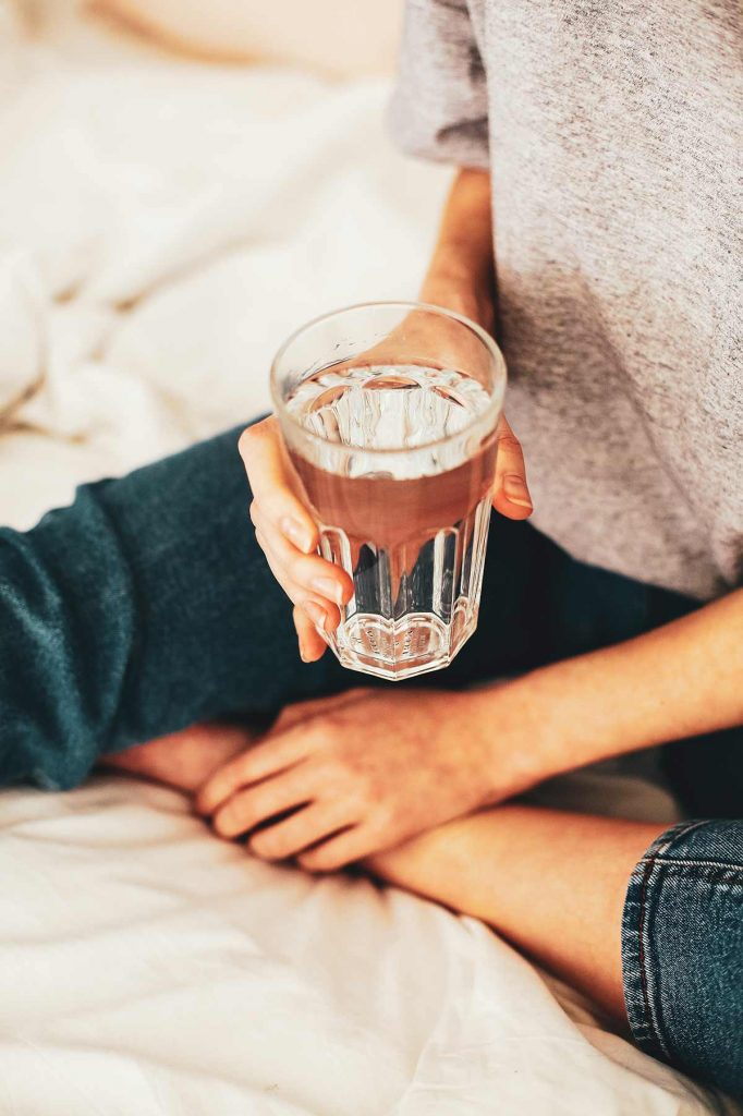 A woman sits on a bed holding a glass of water