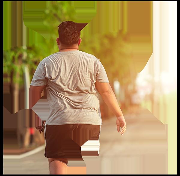 An overweight man walks in a park towards a sunset